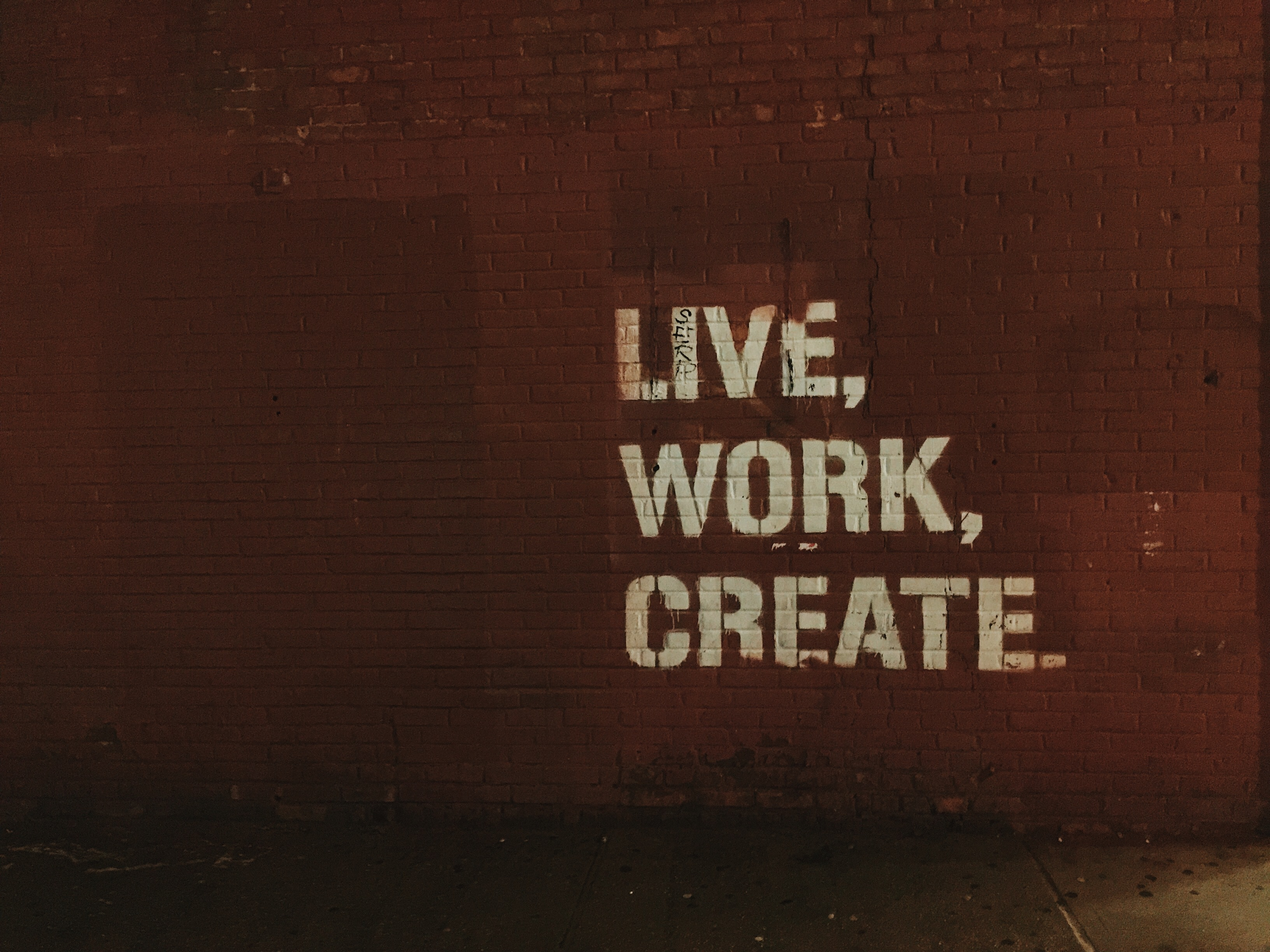 """A brown brick wall with the words """"Live. Work. Create."""" spraypainted on it."""